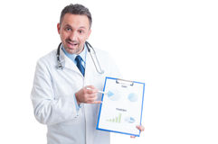Doctor or medic presenting clipboard with sales and prediction c Royalty Free Stock Photography