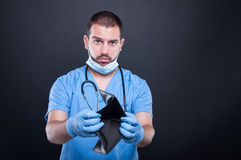Doctor or medic showing empty wallet looking sad Royalty Free Stock Images