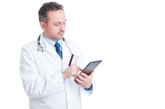 Doctor or medic using credit  card and wireless tablet Stock Image