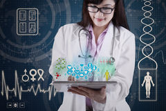 Doctor with medical apps on digital tablet. Female doctor holding tablet pc with medical app Stock Photography