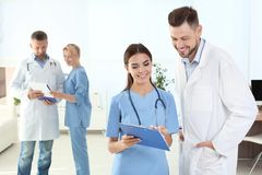 Doctor and medical assistant with colleagues in clinic. Health care service royalty free stock photos