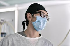 Surgeon in operating room. Doctor in the medical clothes stands in the operating room on the light wall background. He wears a blue mask with black hat and Royalty Free Stock Images