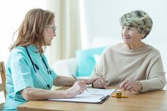 Doctor on medical home appointment. Female doctor on medical home appointment talking with elderly patient stock images