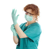 Doctor in medical mask pulling on surgical gloves Stock Images