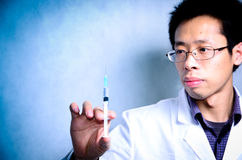 Doctor with medical syringe in hand. Asian man doctor with medical syringe in hand Stock Image