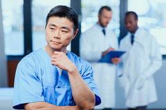 Doctor in medical uniform with collegues behind in clinic Royalty Free Stock Images