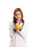 Doctor in medical uniform holding an orange in her hands Royalty Free Stock Photos