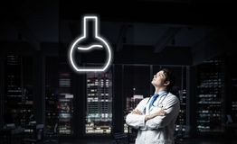 Doctor and medical vial symbol. Horizontal shot of young confident doctor in white medical uniform interracting with glowing vial symbol whie standing against stock images