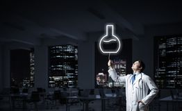 Doctor and medical vial symbol. Horizontal shot of young confident doctor in white medical uniform interracting with glowing vial symbol whie standing against stock photos