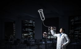 Doctor and medical vial symbol. Horizontal shot of young confident doctor in white medical uniform interracting with glowing vial symbol whie standing against royalty free stock photo