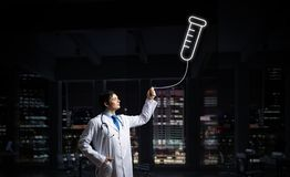 Doctor and medical vial symbol. Horizontal shot of young confident doctor in white medical uniform interracting with glowing vial symbol whie standing against stock photo