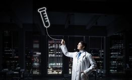 Doctor and medical vial symbol. Horizontal shot of young confident doctor in white medical uniform interracting with glowing vial symbol whie standing against stock image