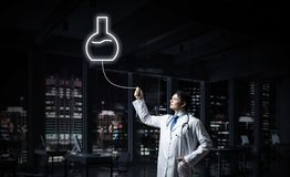 Doctor and medical vial symbol. Horizontal shot of young confident doctor in white medical uniform interracting with glowing vial symbol whie standing against royalty free stock photos