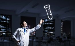 Doctor and medical vial symbol. Horizontal shot of young confident doctor in white medical uniform interracting with glowing vial symbol whie standing against royalty free stock image
