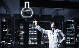 Doctor and medical vial symbol. Horizontal shot of young confident doctor in white medical uniform interracting with glowing vial symbol whie standing against royalty free stock images
