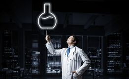 Doctor and medical vial symbol. Horizontal shot of young confident doctor in white medical uniform interracting with glowing vial symbol whie standing against stock photography
