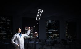 Doctor and medical vial symbol. Horizontal shot of young confident doctor in white medical uniform interracting with glowing vial symbol whie standing against royalty free stock photography