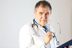 Doctor of medicine looks thoughtfully into the distance holding glasses stock photography