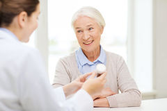 Doctor with medicine and senior woman at hospital Stock Images