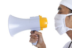 Doctor with megaphone over white. A doctor yelling with megaphone isolated over white background Stock Photo