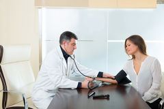 Doctor man checking blood pressure cuff on woman patient Stock Photos
