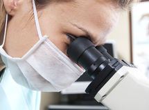 Doctor with microscope. Lady doctor is looking to a microscope in the lab Stock Photo