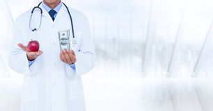 Doctor mid section with apple and money against blurry window Royalty Free Stock Photos