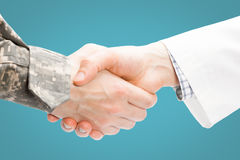 Doctor and military man shaking hands on white background - close up shot on light blue background Royalty Free Stock Images