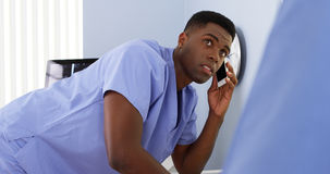 Doctor on mobile talking to colleague and using computer. African American male doctor on mobile talking to colleague and using computer Royalty Free Stock Images