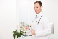 Doctor with money. Royalty Free Stock Photo