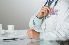 Doctor with money Royalty Free Stock Photos