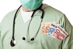 Doctor with money in his pocket. Close up of doctor with stethoscope and money in his pocket Stock Image