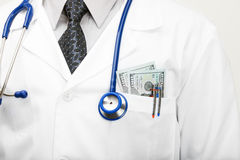Doctor with money in his pocket - studio shoot Stock Photo