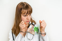 Doctor with money in pocket and handcuffs. Corruption and bribe concept in medicine Royalty Free Stock Images