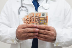 Doctor with money in studio Stock Image