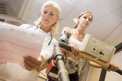 Doctor Monitoring Female Patient On Treadmill Stock Photography