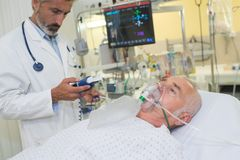 Doctor monitoring patient wearing oxygen mask. Patient stock photography