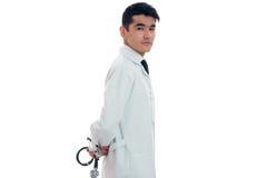 Doctor moreno adulto joven del hombre en uniforme con el estetoscopio en sus manos que presentan en la cámara aislada en el fondo Imagen de archivo libre de regalías