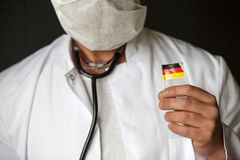 Doctor with mouthguard holding a german flag Royalty Free Stock Photos