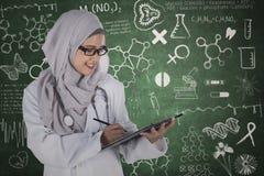 Doctor musulmán con el tablero y garabatos Foto de archivo libre de regalías
