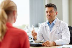 Doctor with nasal spray and patient at hospital Stock Photo