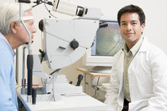 Doctor Next To Equipment To Detect Glaucoma Royalty Free Stock Photography