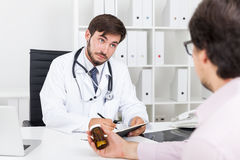 Doctor not buying new drug. Bearded doctor not believing to his patient's lies about healthy lifestyle and not taking alcohol at all. Concept of everybody lies Royalty Free Stock Photos