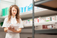 Doctor with a notebook in her hands in the drug store Royalty Free Stock Photo