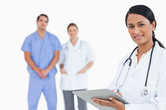 Doctor with notepad and colleagues behind her Royalty Free Stock Photo