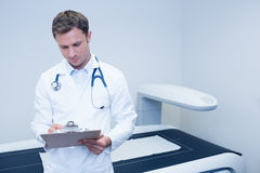 Doctor noting something on his clipboard Royalty Free Stock Photography