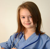 Doctor or nurse. Little girl dressed in scrubs with stethoscope around neck Royalty Free Stock Images