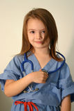 Doctor or nurse. Little girl dressed in scrubs with stethoscope around neck Royalty Free Stock Photo