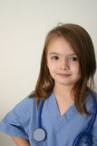 Doctor or nurse. Little girl dressed in scrubs with stethoscope around neck Stock Images