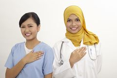 Doctor and nurse. Asian nurse and doctor with welcome hand sign on the white background Royalty Free Stock Photography